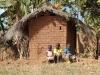 3 kids by their hut
